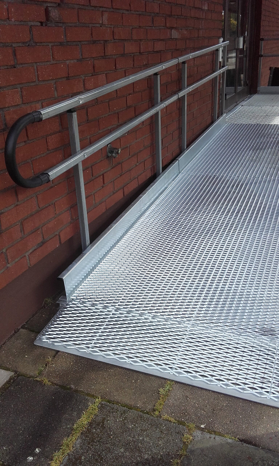 A wheelchair ramp in front of a brick building
